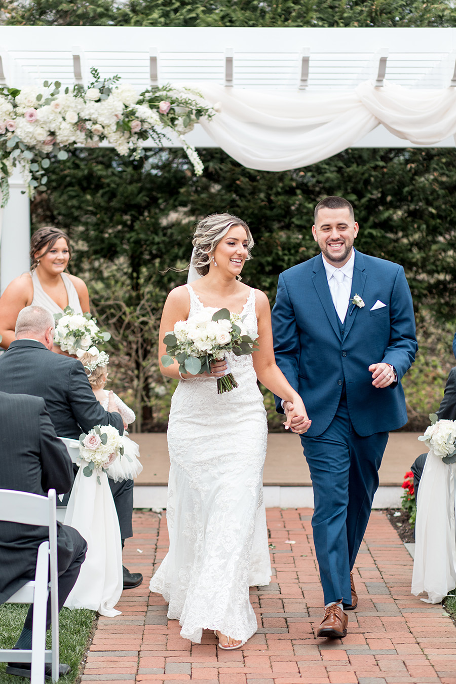 bride and groom walk down the aisle together at their outdoor ceremony at the Bradford Estate