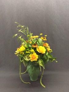 Picture of green vase with seasonal flower arrangement.