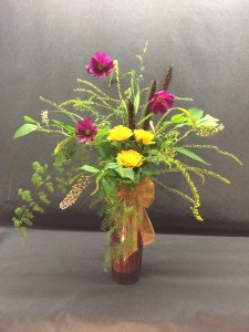 Picture of red ceramic vase filled with roses, Cosmos, Solidago and more.