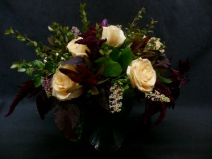 picture arrangement of peach-butter Roses combined with dark red Amaranth.