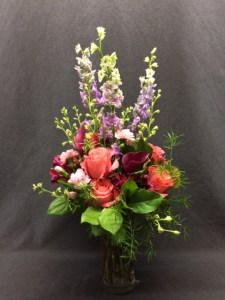 picture of arrangement featuring Pink Rose and violet Larkspur.