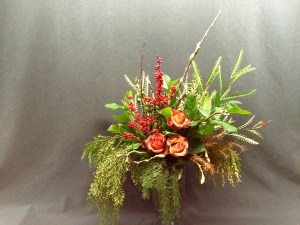Dusky Red Christmas arrangement with Roses, Ilex, Grevillia, Cedar Magnolia buds and more.