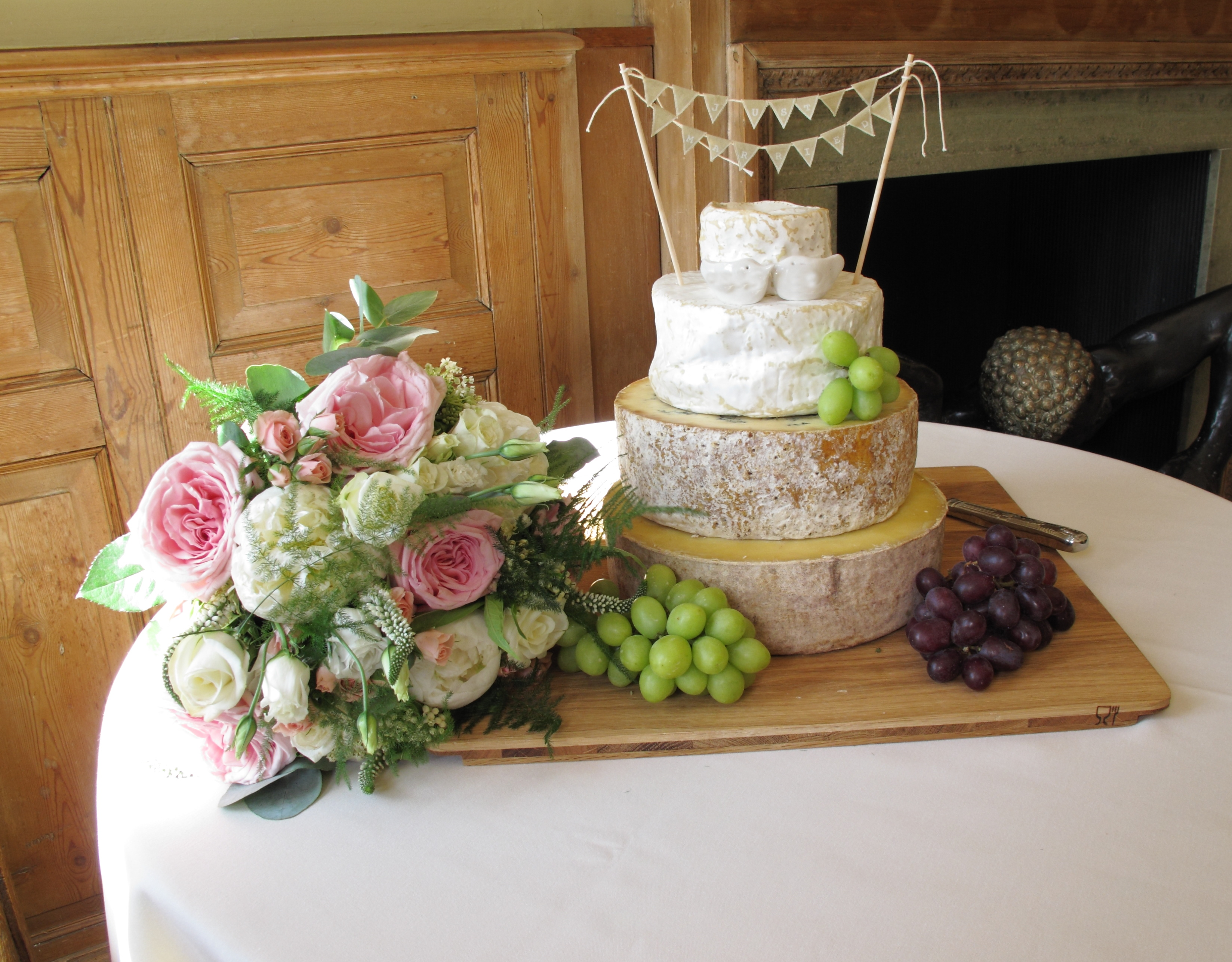 Pink and white wedding bouquet next to cake of cheeses