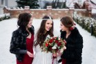 Bridesmaids in black fur coats and red dressed surround pretty bride