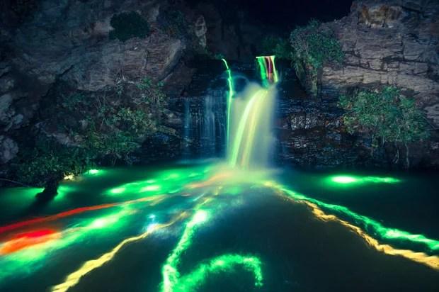 Colorful Long Exposure Photos of Glow Sticks Dropped Into Waterfalls glowwaterfall 1