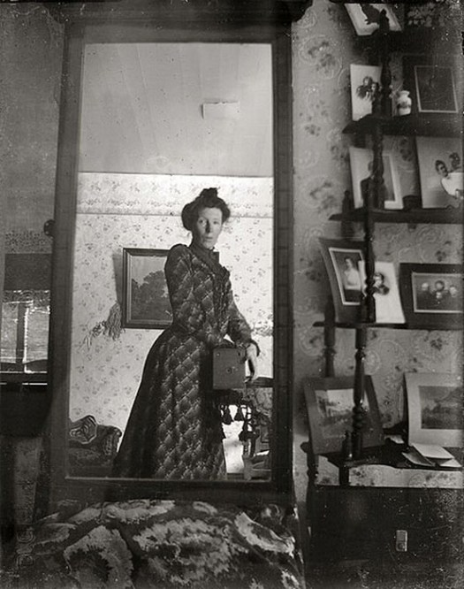 unidentified_woman_taking_her_own_photograph_using_a_mirror_and_a_box_camera_roughly_1900-2