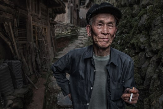 Chinese man from the Longji area takes a break outside his house.