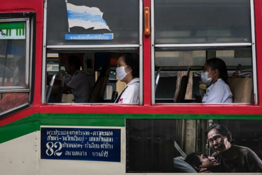 """Another off-the-cuff shot but this caught my eye - the people wearing masks on the bus seemed to tie in with the sad """"hospital"""" image on the side of the bus. Even the red marks on the left hand person's shirt reminded me of blood."""