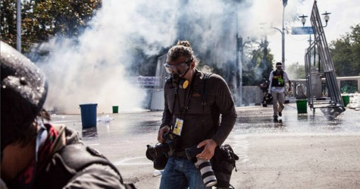 Freelance photographer and FFR member Bill Kotsatos is seen during clashes between anti-government protestors and riot police, 01 December 2013, in central Bangkok, Thailand. (© Adam Gnych)
