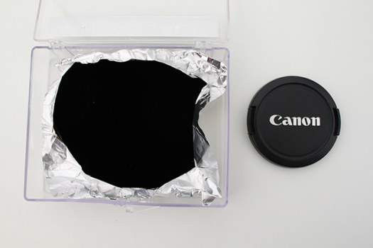 A Vantablack sheet of aluminum foil next to a Canon lens cap. Photo by Engineering & Technology