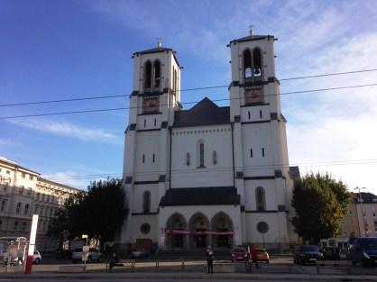 ฝั่งตรงข้ามจะเป็นโบสถ์ St. Andrä แท่นที่เห็นอยู่ริมถนนทางด้านซ้ายคือสัญลักษณ์ของป้ายรถบัส จะมีรายละเอียดรถบัสที่วิ่งผ่านกับรอบรถแปะอยู่