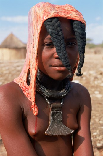 A Himba girl is shown with cow peritoneum on her head. Photo by indigenous person and conservation photographer Pete Oxford.