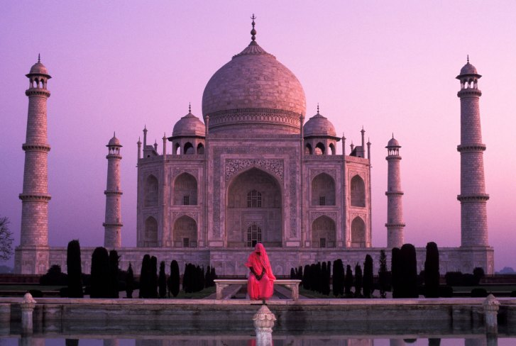 The Taj Mahal is lit with soft warm pink light as a woman sits alone in front of it in a pink sari. Photo by travel photographer and conservation photographer Pete Oxford.