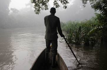 A man paddles from the front of a canoe down the Lekoli River. Photo by travel photographer and conservation photographer Pete Oxford.
