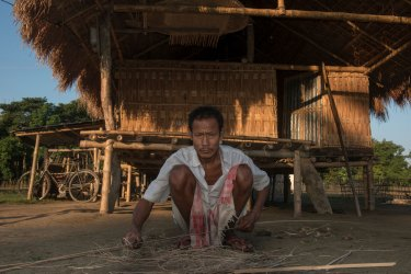A man crouches over cane for basket weaving. Photo by indigenous people photographer Pete Oxford.