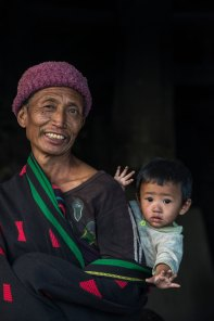 A Konyak Naga man smiles while holding a child on his back. Photo by indigenous person photographer Pete Oxford.