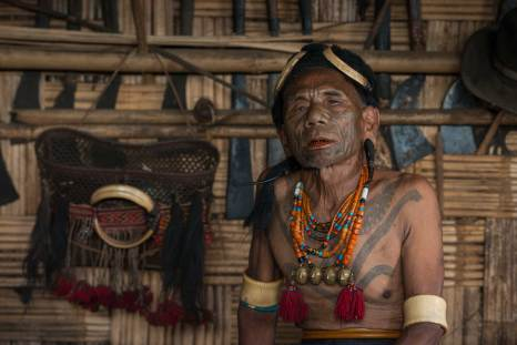 An indigenous Konyak Naga tattooed head hunter shows off his traditional dress. Photograph by conservation photographer and cultural photographer Pete Oxford.