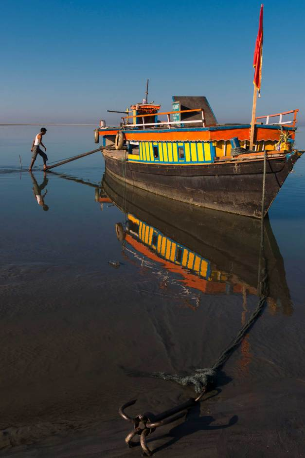 A ferry sits on the mirror-like Brahmaputra River. Photograph by conservation photographer and cultural photographer Pete Oxford.