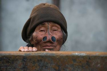 A native Apatani woman looks on with facial tattoos and nose plugs. Photo by conservation photographer and cultural photographer Pete Oxford.