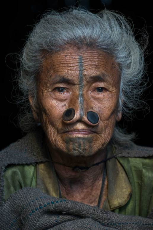 A native Apatani woman sits with facial tattoos and nose plugs. Photograph by conservation photographer and cultural photographer Pete Oxford.