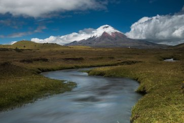 Cotopaxi Volcano sits in the background with a winding stream leading towards it. Photograph by landscape photographer Pete Oxford.