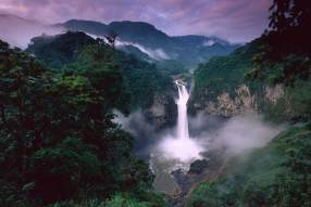 San Rafael waterfall flows beneath a purple sky. Photo by conservation photographer and landscape photographer Pete Oxford.