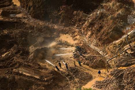 Workers spray water on a gold mining site. Photo by conservation photographer Pete Oxford.