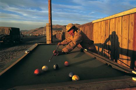 A man plays snooker on the side of the street in Mongolia. Photo by travel photographer and conservation photographer Pete Oxford.