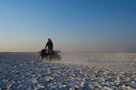 A man on an ATV rides through a snow covered plain. Photo by travel photographer Pete Oxford.