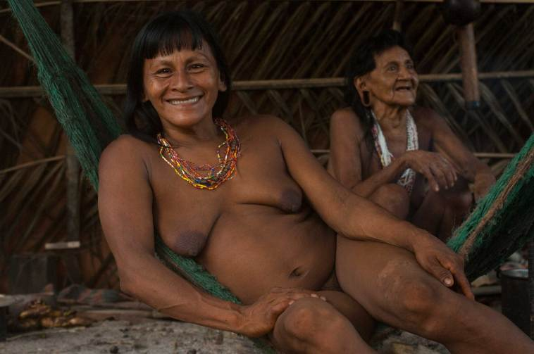 Native women rest in hammocks in their hut in their territory in Yasuni National Park. Photo by conservation photographer and cultural photographer Pete Oxford.