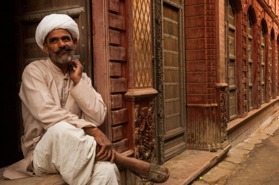 A man sits on the edge of a havelis in Bikaner. Photo by indigenous person photographer Pete Oxford.