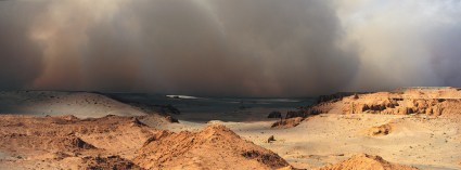 A massive sandstorm is shown in the distance. Photo by landscape photographer Pete Oxford.