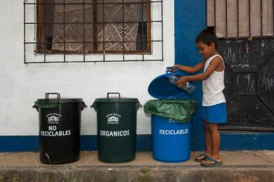 A boy places an empty water bottle in the recycling bin at the Recycle Center for town of Puerto Ayora. All glass, plastic, bottles and cardboard are recycled and sent to the mainland for re-processing. Photograph by conservation photographer Pete Oxford.