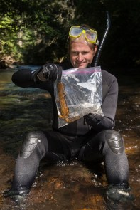 A man holds a hellbender salamander for research study. Photo by conservation photographer Pete Oxford.