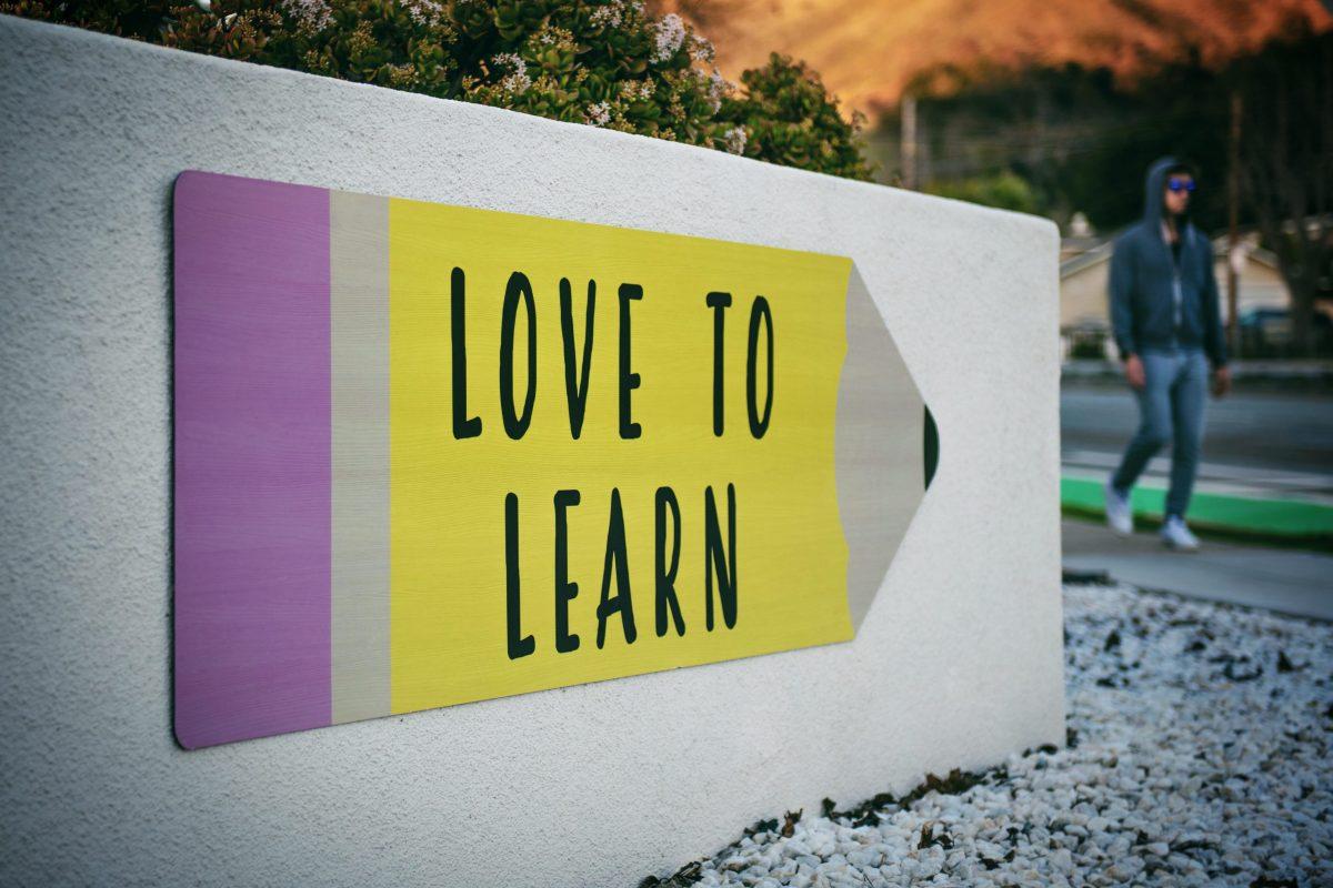 """Eine große Tafel mit einem riesigen Bleistift, der mit """"Love to Learn"""" beschriftet ist"""