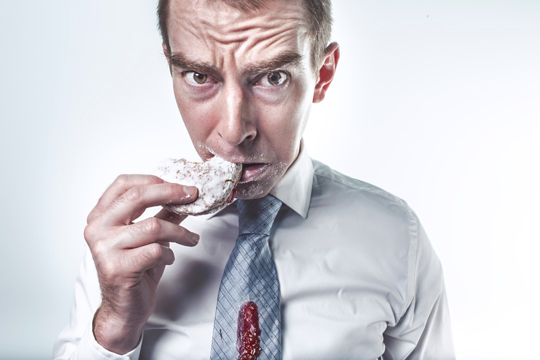 a man falling into the obese dieting trap and feeling guilty for eating a donut