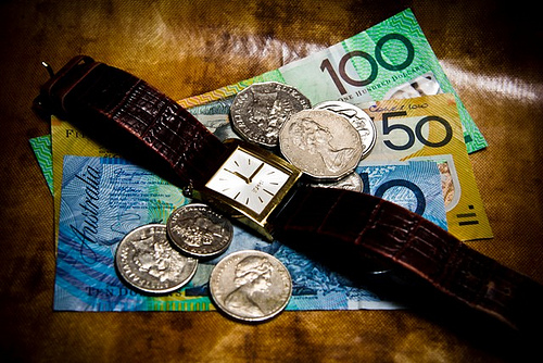 Time is money. Australian currency and a wrist watch.