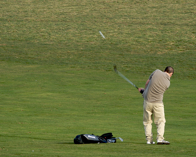Amateur golfer hitting a ball.
