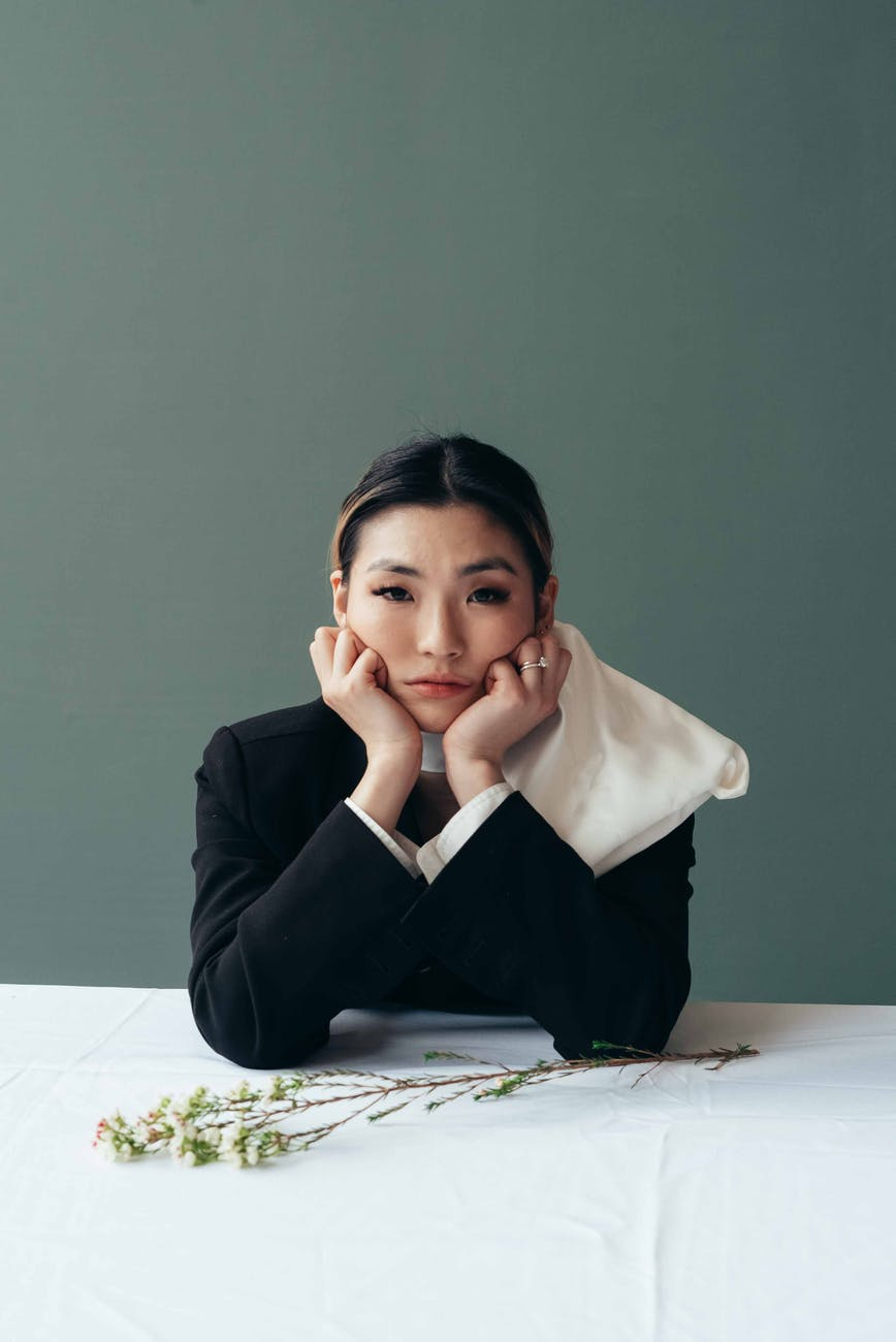 asian woman leaning on hands at table with flower