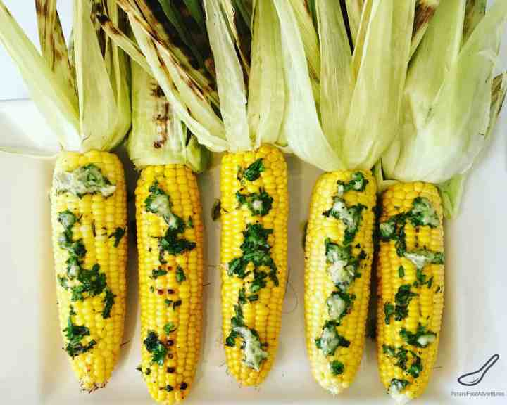 Grilled Corn on the Cob in husks smothered in fresh herb butter