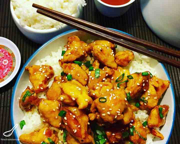 Chinese Honey Sesame Chicken over rice with chopsticks on a table