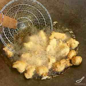 Frying battered chicken pieces in a wok