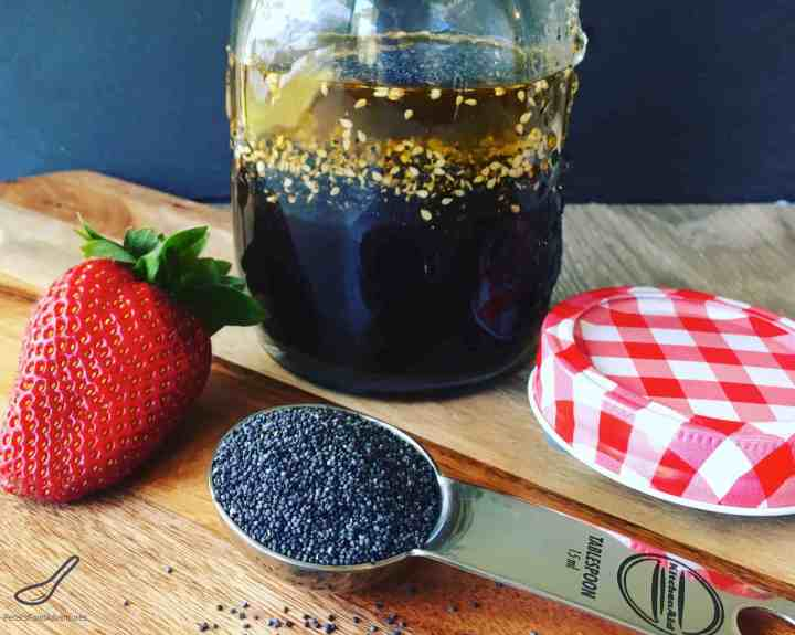 Jar of Poppy Seed Salad Dressing with a spoon of Poppy Seeds