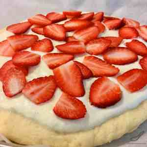 A baked brioche style yeast bun generously smothered with sweet Tvorog, Farmer's Cheese or Quark and baked with fresh strawberries. Russian Pastry Sweet Bread Dessert (Сдобный пирог)