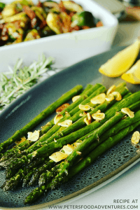 Asparagus on a platter with garlic and lemon