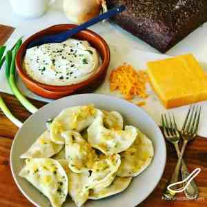 This Potato Cheddar Perogy Recipe is a Canadian and American Classic dish with roots in Poland and Eastern Europe. Boiled or fried, served with sour cream, Potato and Cheddar dumplings, the perfect comfort food!