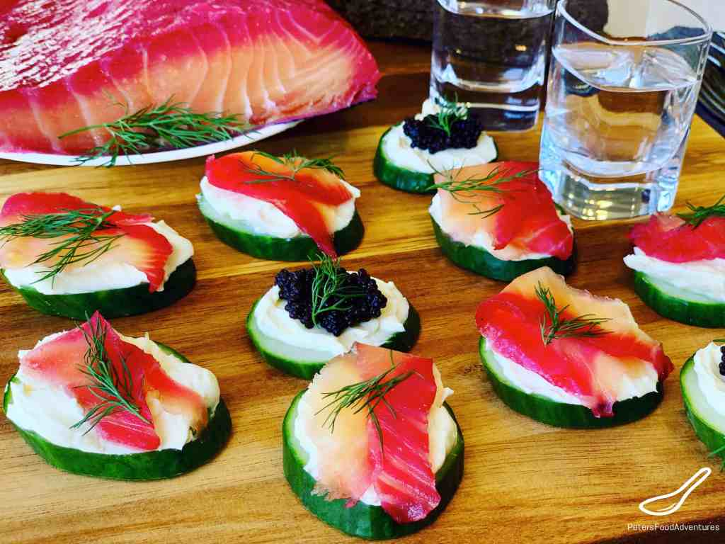 Cucumber Appetizers with Salmon and caviar on a wooden board, with a shot of vodka