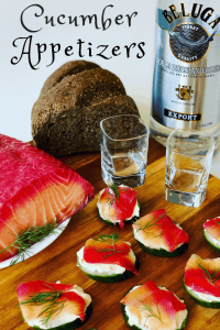 Cucumber Zakuski Appetizers with Salmon on a cutting board with rye bread and a bottle of vodka