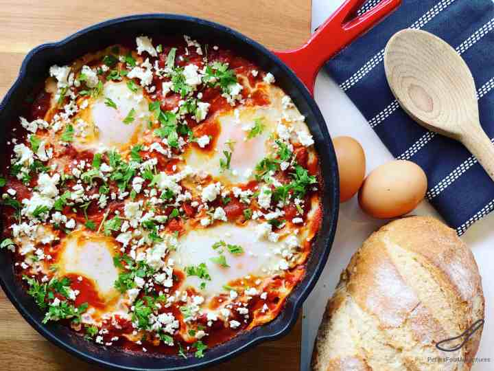 Shakshouka eggs in a iron skillet on a table with a loaf of bread, wooden spoon and tea towel