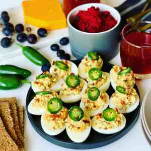 Jalapeno Deviled Eggs on a plate surrounded by dips, cheese, jalapenos and grapes